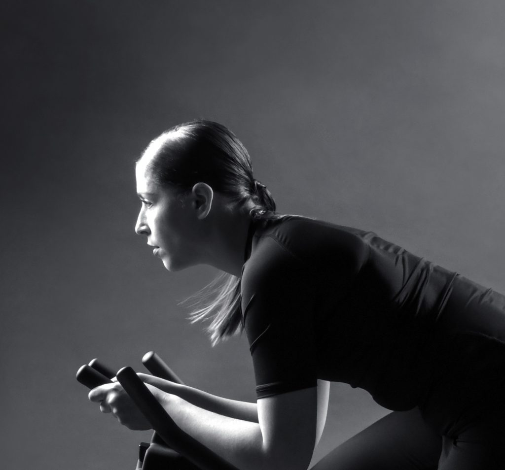 Mujer practicando ciclismo indoor